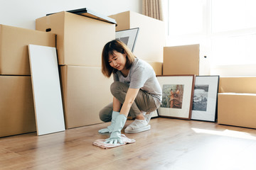 Young woman polishing wooden floor at new home