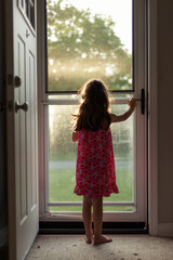 Girl in pajamas looking out front door early on a sunny morning