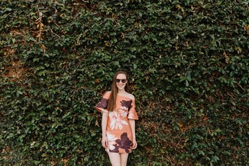 Young Woman on a Wall of Shrubs