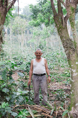 Smiling portrait of local farmer working in coffee plantation in