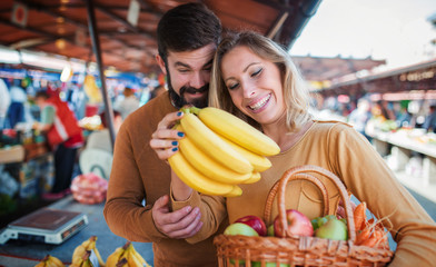 Young couple buying at street market. Lifestyle, consumerism, shopping