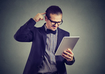 Confused man watching tablet on gray