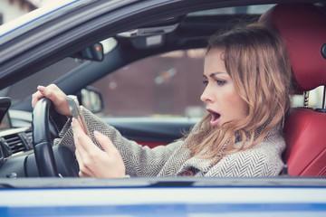 Shocked girl watching phone in car