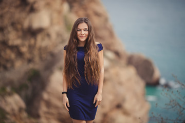 A young beautiful happy girl in a tight dark blue dress dreams above the sea. Blurred rocks and cliffs on background. Horizontal orientation. Copy space
