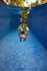 Child underwater with a snorkel set in a deep blue swimming pool