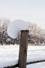 Leaning snow cap shaped by the wind on a wodden fence