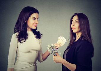 Women holding money exchanging with each other dollars to euro cash