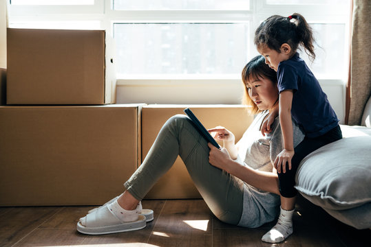 Adorable girl and her mother using digital tablet and moving