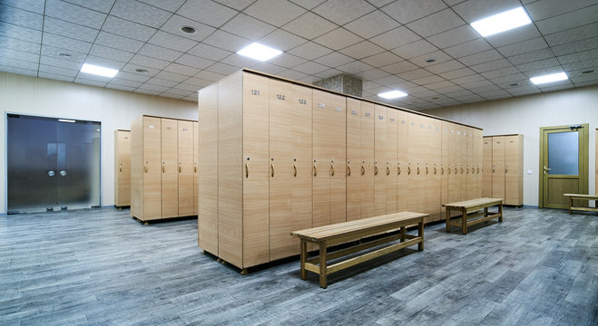 Interior of a locker room. Clean empty dressing room with big lockers and wooden bench