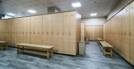 Interior of locker room in the gym. Sportsmen locker room with bench