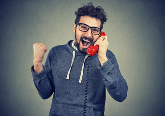Excited man receiving good news on a phone