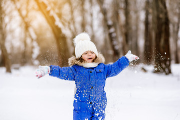 Little cute girl, throwing snow, happy and fun. Beautiful girl is walking in the park in winter.