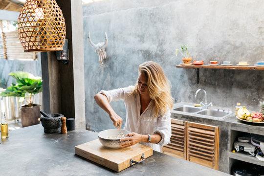Woman preparing home made tortillas in trendy concrete kitchen