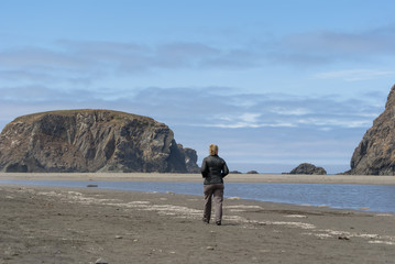 Woman taking early morning walk at Whaleshead Beach on the Oregon Coast.