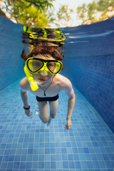 Boy wearing a snorkel and mask under water in a swimming pool