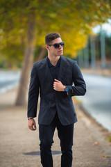 Good looking man in fashion shoot, wear black dress shirt and sunglasses walking on the street