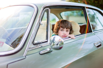 Boy sitting in a classic car with window open