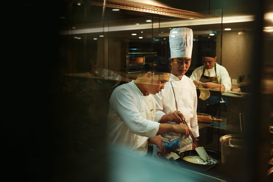 Trainee cooking with chef in kitchen