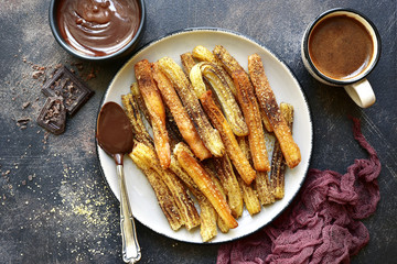 Churros - traditional mexican dessert with chocolate sauce.Top view .