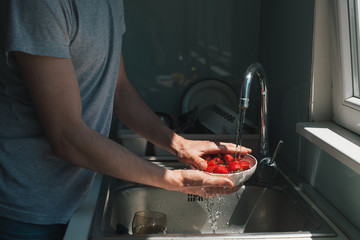 Man rinsing strawberries