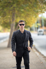 Good looking man in fashion shoot, wear black dress shirt and sunglasses walking on the street