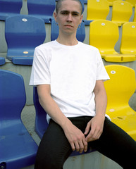 Young man sitting on colourful stadium seats