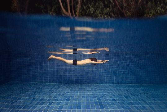 Boy in a swimming pool under water