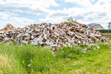 Huge pile of burning fire log wood in a green field