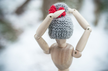 closeup of wooden puppet with wool hat - in the snow - concept winter fashion