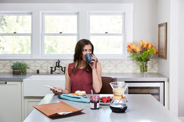 Beautiful young woman texting at home while eating breakfast