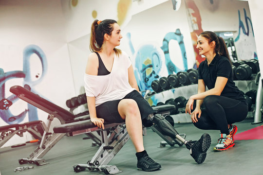 Disabled woman exercising with personal trainer