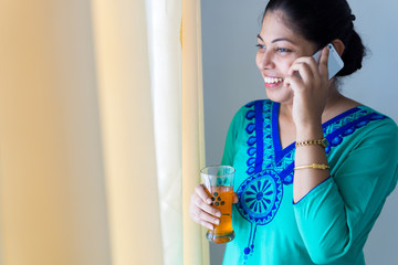 Happy woman drinking juice and talking on mobile phone