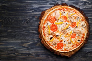 Appetizing pizza with tomato, chicken, paprika and mushrooms, top view with copy space. Delicious Italian food, restaurant menu photo