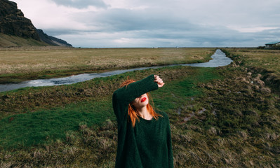 ginger woman covering her eyes in a beautiful landscape