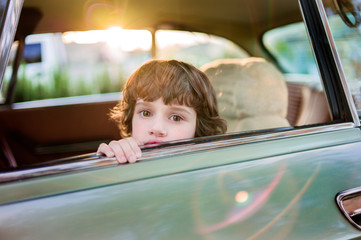 Boy peeking out an open car window, with flare
