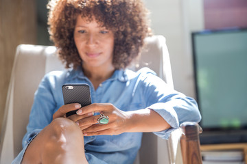 Woman relaxing at home while reading on her smartphone