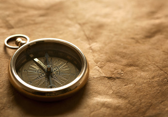 antique compass on vintage paper background