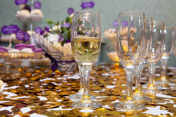 Glasses with champagne on the background of a festively decorated table with desserts
