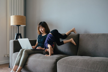 Adorable girl playing on sofa, her mom working on laptop