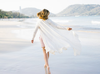 Romantic woman walking on beach