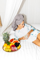 Young adult female wearing towel on head laying in bed eating fruit with glass of sparkling water