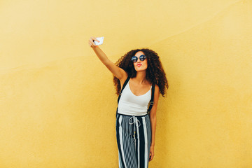 Portrait of a chic tourist taking a selfie in front of a yellow wall.