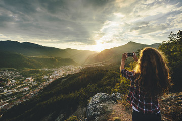 Young woman taking a picture in the mountain