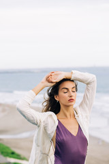 Beautiful Caucasian Woman Posing With Closed Eyes on Windy Beach