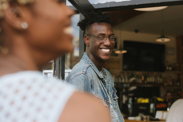 Young man laughing with girlfriend at bar