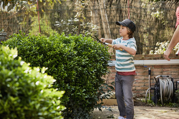 Boy Cutting Plants With Pruning Shears