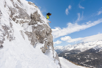 Man with skis jumping off high cliff covered in snow