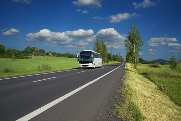 Fotobehang - White bus traveling on asphalt road in a rural landscape. Village and mountain with castle ruins in the background.