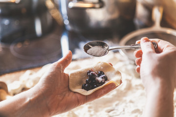 Hand of woman pouring sugar into dumpling with black berries