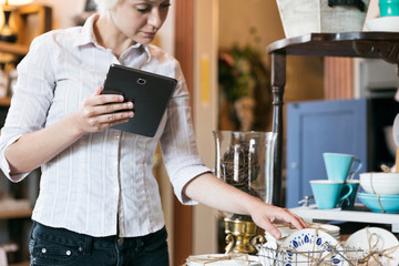 Shop: Woman Uses Digital Tablet While Checking Inventory